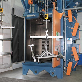 Shot blast machines with overhead conveyor